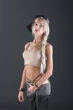 Attraktive blonde Frau auf grauem Hintergrund Lizenzfreie Stockfotografie