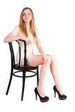 Attraktive blonde Frau auf Stuhl Lizenzfreies Stockbild