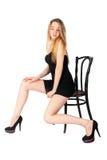 Attraktive blonde Frau auf Stuhl Lizenzfreies Stockfoto