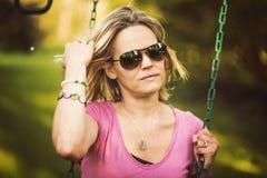 Attraktive blonde Frau auf Swingset Lizenzfreie Stockfotografie