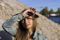 Attraktive blonde Frau bei Sonnenuntergang mit Sonnenbrille in der Hand Stockfotos