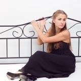 Attraktive blonde Frau in der eleganten fashiontable schwarzen Kleiderlüge auf Bett Lizenzfreies Stockbild