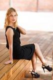 Attraktive blonde Frau in der eleganten schwarzen Kleidung, die auf Bank stillsteht Stockfotografie