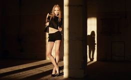 Attraktive blonde Frau in der schwarzen Kleidung Stockfotos