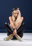 Attraktive blonde Frau, die auf blauem Hintergrund sitzt Stockfotos