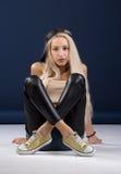 Attraktive blonde Frau, die auf blauem Hintergrund sitzt Stockfoto