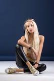 Attraktive blonde Frau, die auf blauem Hintergrund sitzt Lizenzfreies Stockbild