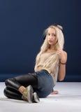 Attraktive blonde Frau, die auf blauem Hintergrund sitzt Lizenzfreie Stockfotografie