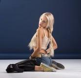 Attraktive blonde Frau, die auf blauem Hintergrund sitzt Lizenzfreie Stockbilder