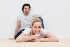 Attraktive blonde Frau, die auf dem Boden liegt Lizenzfreie Stockbilder