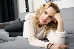 Attraktive blonde Frau, die auf dem Sofa in ihrem Haus sich entspannt Stockbilder