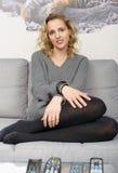 Attraktive blonde Frau, die auf dem Sofa in ihrem Haus sich entspannt Stockfoto