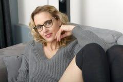 Attraktive blonde Frau, die auf dem Sofa in ihrem Haus sich entspannt Lizenzfreies Stockbild