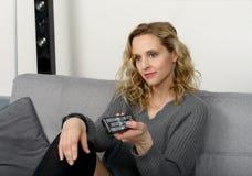 Attraktive blonde Frau, die auf dem Sofa in ihrem Haus sich entspannt Lizenzfreie Stockfotografie