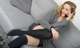 Attraktive blonde Frau, die auf dem Sofa in ihrem Haus sich entspannt Lizenzfreie Stockfotos