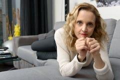 Attraktive blonde Frau, die auf dem Sofa in ihrem Haus sich entspannt Stockfotos