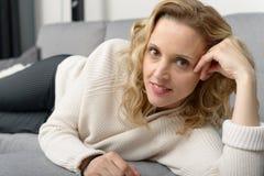 Attraktive blonde Frau, die auf dem Sofa in ihrem Haus sich entspannt Stockbild