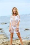 Attraktive blonde Frau, die auf dem Strand steht Stockfotos