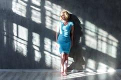 Attraktive blonde Frau, die auf der Wand und dem Schauen sich lehnt Lizenzfreies Stockbild