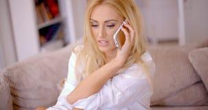 Attraktive blonde Frau, die auf einem Mobile plaudert Lizenzfreies Stockfoto