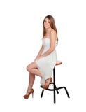 Attraktive blonde Frau, die auf einem Schemel sitzt Stockbild