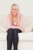 Attraktive blonde Frau, die auf einem Sofa aufwirft Lizenzfreies Stockfoto