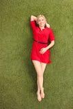 Attraktive blonde Frau, die auf Gras liegt Stockbilder