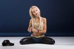 Attraktive blonde Frau, die auf ihren Knien sitzt Stockbild