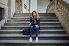Attraktive blonde Frau, die auf Steinschritten sitzt Lizenzfreies Stockfoto