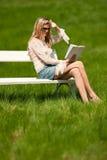 Attraktive blonde Frau, die auf weißer Bank sitzt Lizenzfreies Stockfoto