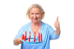 Attraktive blonde Frau, die brennende Kerzen hält Lizenzfreie Stockfotos