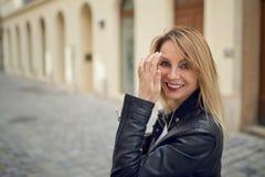 Attraktive blonde Frau, die draußen in einem Hof schlägt ihr langes blondes Haar steht Stockbild