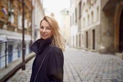 Attraktive blonde Frau, die draußen in einem Hof schlägt ihr langes blondes Haar steht Lizenzfreies Stockfoto
