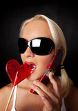 Attraktive blonde Frau, die durch Mobiltelefon benennt Stockbild