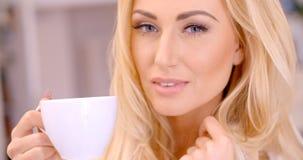Attraktive blonde Frau, die ein Heißgetränk genießt Stockbilder