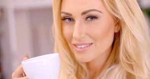 Attraktive blonde Frau, die ein Heißgetränk genießt Lizenzfreies Stockbild