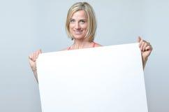 Attraktive blonde Frau, die ein leeres Zeichen hält Stockbild