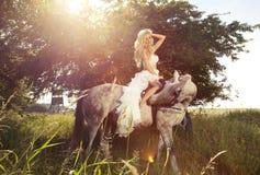 Schönes Foto der blonden sinnlichen Braut, die ein Pferd reitet. Stockbild