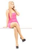 Attraktive blonde Frau, die an einem Telefon spricht und auf einer Tabelle sitzt Stockbilder