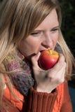 Attraktive blonde Frau, die in einen Apfel beißt Lizenzfreies Stockbild