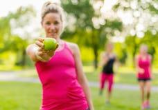 Attraktive blonde Frau, die einen Apfel nach einem Stoß isst Lizenzfreies Stockbild