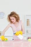 Attraktive blonde Frau, die einen Ausschnittvorstand säubert Stockfoto