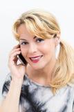 Attraktive blonde Frau, die einen Handy verwendet Stockfotografie