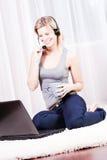 Attraktive blonde Frau, die einen Kopfhörer und einen Spaß trägt Lizenzfreie Stockfotos