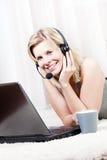 Attraktive blonde Frau, die einen Kopfhörer und einen Spaß trägt Stockbilder