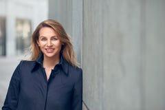 Attraktive blonde Frau, die an einer städtischen Betonmauer sich lehnt Stockfoto