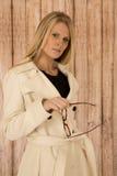 Attraktive blonde Frau, die Gläser im weißen Mantel mit woode hält Stockbilder