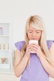 Attraktive blonde Frau, die heißes Getränk trinkt Stockbilder