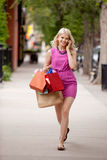 Attraktive blonde Frau, die hinunter Straße geht Lizenzfreie Stockbilder