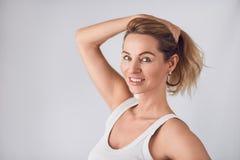 Attraktive blonde Frau, die ihr langes Haar hält Stockfotos